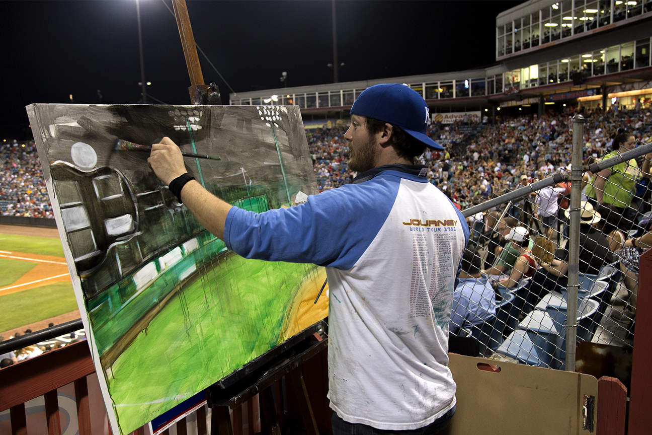 Painter and Kansas City Royals fan Anthony Billups paints Greer Stadium while the last game is being played.